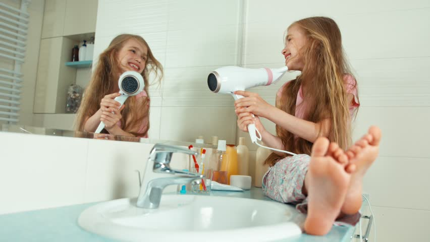 Girl 7-8 years old dries her long blonde beautiful hair with a hair dryer in the bathroom and smiling at camera. Zooming