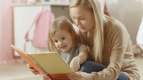 Beautiful Young Mother and Her Cute Little Daughter Read Children's Book Together. Children's Room is Pink and Full of Toys. Shot on RED EPIC-W 8K Helium Cinema Camera.