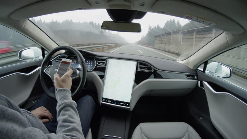 LJUBLJANA, SLOVENIA - FEBRUARY 4, 2017: Tesla Model S autonomous electric car autopilot selfdriving in bad weather condition on highway with no human intervention. Driver writing mail on mobile device