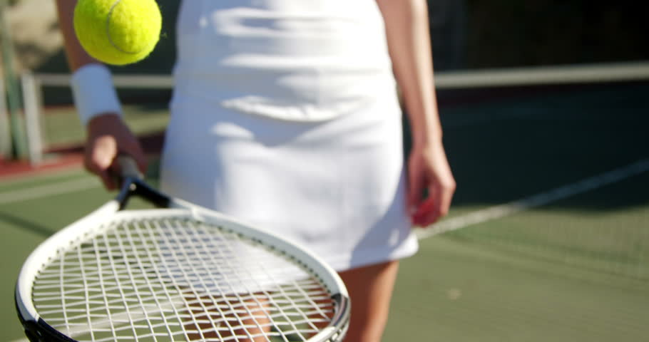 Mid-section of sportswoman practicing tennis on a sunny day