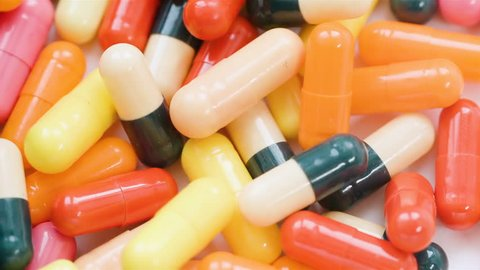 Huge number of pills falling on white background top view in slow motion. Multi-colored tablets are flying.Beautiful drop pills on the table. Green, blue and yellow pills flying. POV drugs slowmotion