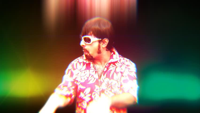A crazy DJ loosing it whilst in the midde of an acid trip on the dance floor. Medium shot. Bizarre silly weirdo.