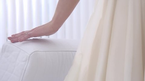 Young beautiful girl touches hand couch. A gentle touch of a hand on a white pillow in slow motion. Slow motion family home part 9 of 15.