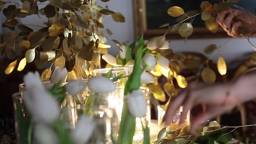 Florist at work. White Tulips in Clear Glass Vases, Golden Flowers on the Table #24324668
