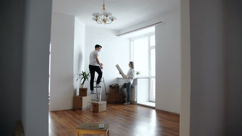 young couple choosing point for picture on wall at home