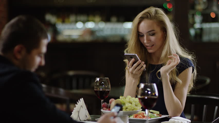 woman showing a site on smartphone phone to a man in cafe