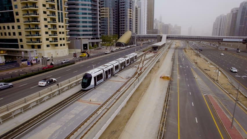 modern tram travels on rails along the high-rise buildings in Dubai, UAE