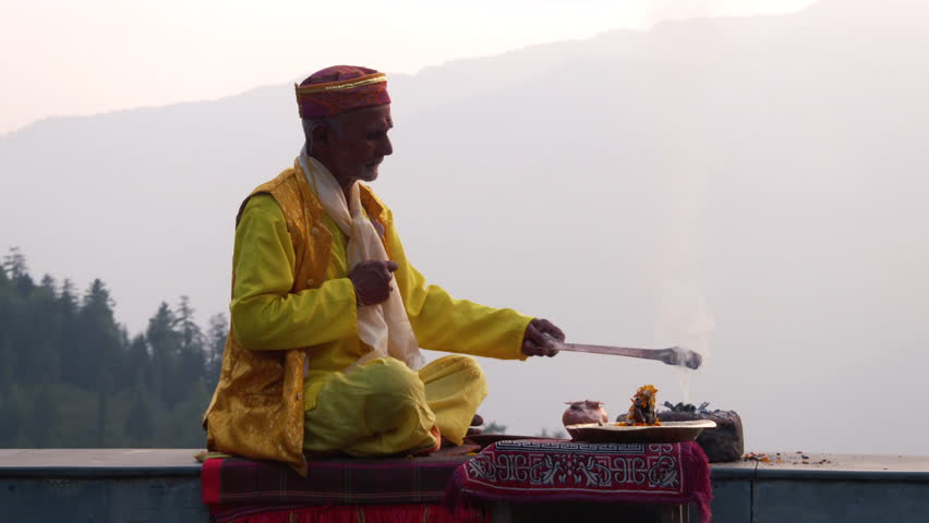 A Hindu old man in yellow national costume offering special spiritual prayer to god in the foothills of the Himalayas, Kullu Valley, India | Shutterstock HD Video #24364034