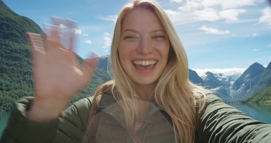 Beautiful woman having video chat using smartphone outdoors sharing travel adventure  friends showing lake and glacier Girl filming selfie video photo for social media  Norway vacation slow motion #24370124