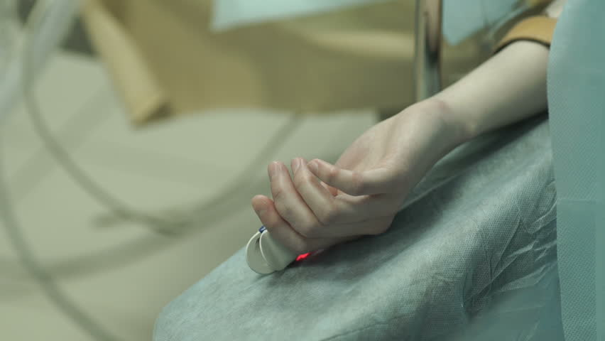 the patient's hand with a heart rate monitor