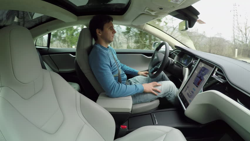 AUTONOMOUS TESLA CAR, FEBRUARY 2016:  Male driver sitting behind the steering wheel and enjoying relaxing and comfortable ride in autonomous self-driving autopilot Tesla Model S driverless car #24380084