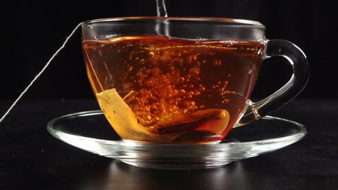 Pouring a tea in transparent cup with hot water and teabag on black background, slow motion 100 fps