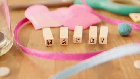 "Moving right to left along a table strewn with delightful coloured craft supplies and coming to rest on the word ""MAKE!"" spelled out with wooden blocks."