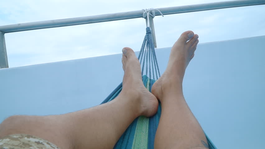 Feet of a man lying down and swinging in a hammock. Full HD stock footage. | Shutterstock HD Video #24389513