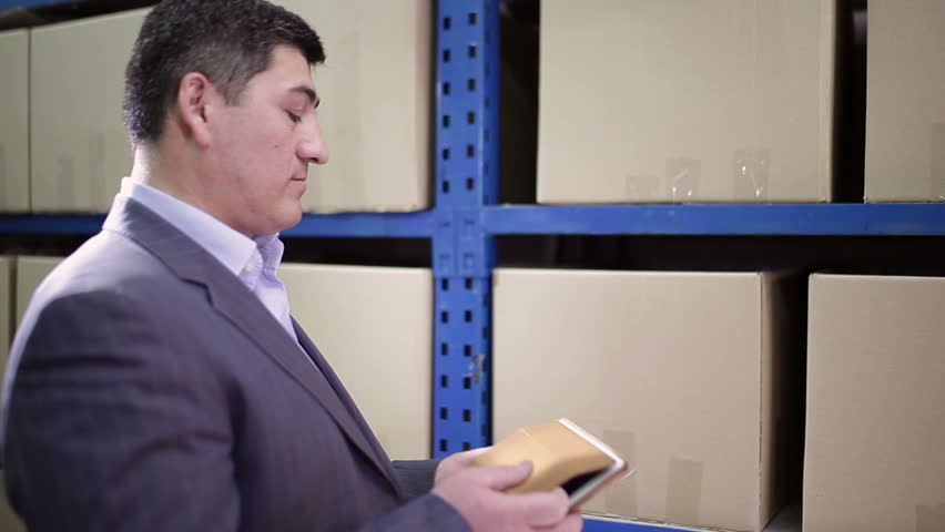 Man stands in the warehouse and keeps the tablet. | Shutterstock HD Video #24414884