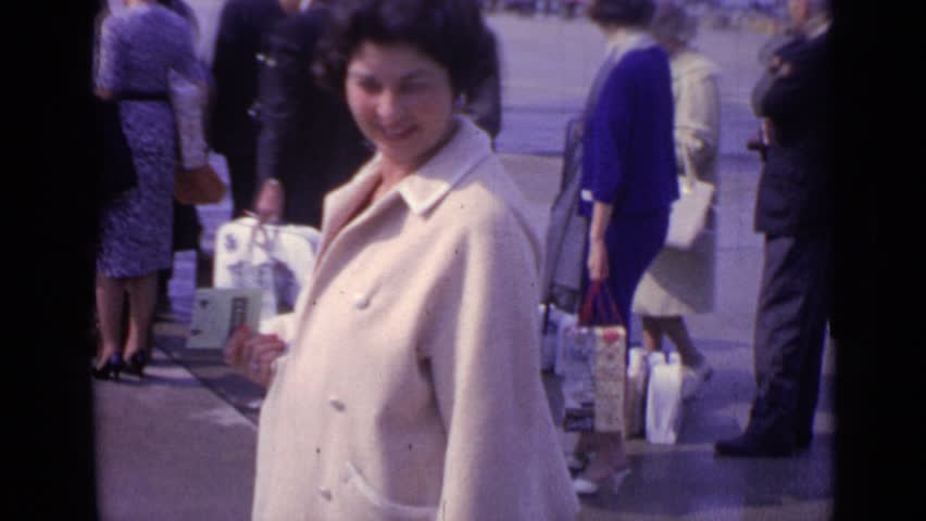 LONDON ENGLAND 1962: lovely lady traveler, captured, sometime during 1950's or 60's, organizing her belongings. #24420404