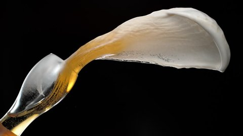 Beer spilled out of glass and making splash. Shot with high speed camera, phantom flex 4K. Slow Motion.