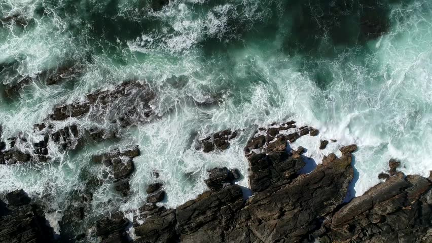 Black Start, Motion Video Background Loop of Aerial Coastline view and waves crashing on rocky cliff shoreline. Location: Fleurieu Peninsula, South Australia. (Black start and end for looping)
