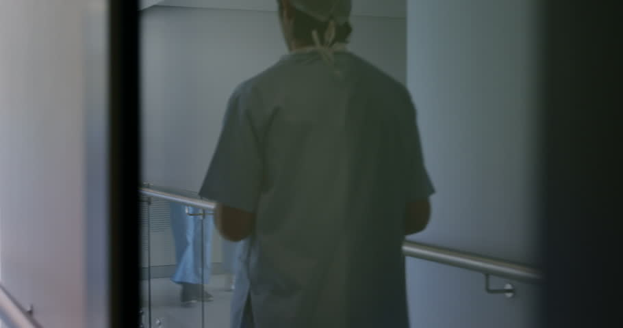 Team of surgeons discussing over medical reports in hospital corridor | Shutterstock HD Video #24464024