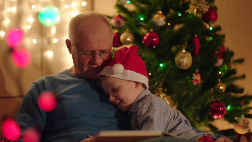 4k0008little boy felling asleep during his gradpa reading book to him on christmas eve - Grandpa For Christmas