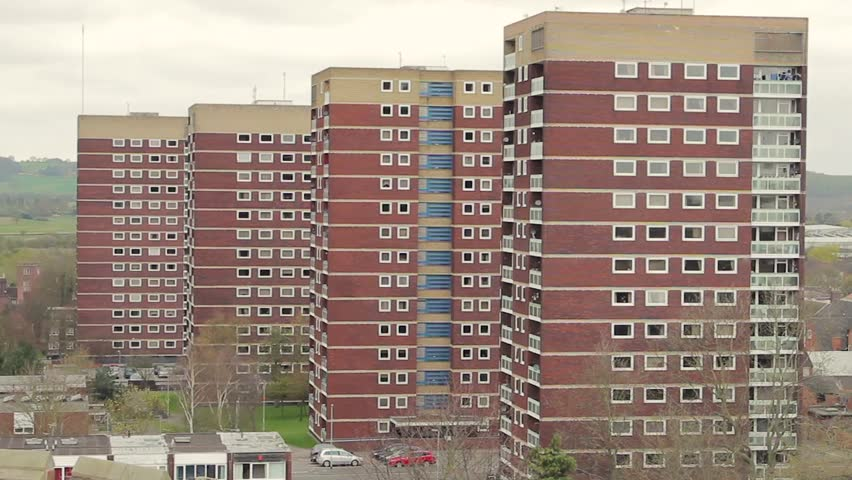 Three matching grimy tower blocks blend together in Tamworth, a bird flies past the deserted urban council estate.  Black and empty windows stare out. | Shutterstock HD Video #24484751