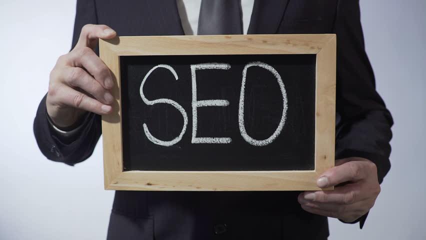 SEO written on blackboard, businessman holding sign, business concept, strategy | Shutterstock HD Video #24503594