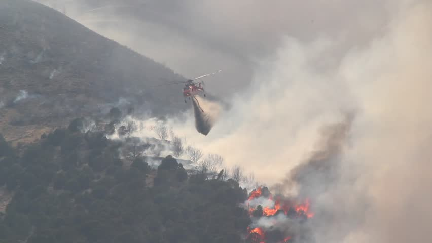 A helicopter battles a gigantic wildfire on a dry mountainside, dropping hundreds of gallons of water on the flames. #2450504