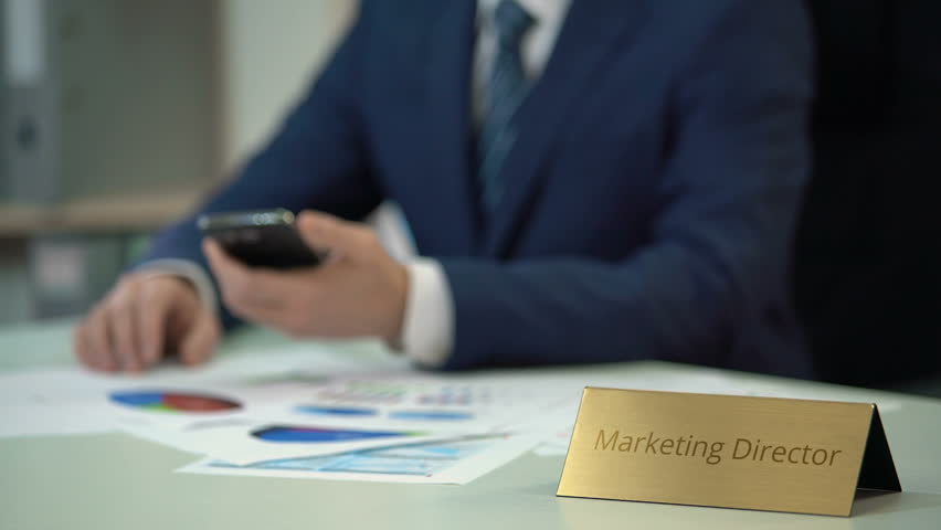 Corporate marketing director analyzing market research data, using smartphone