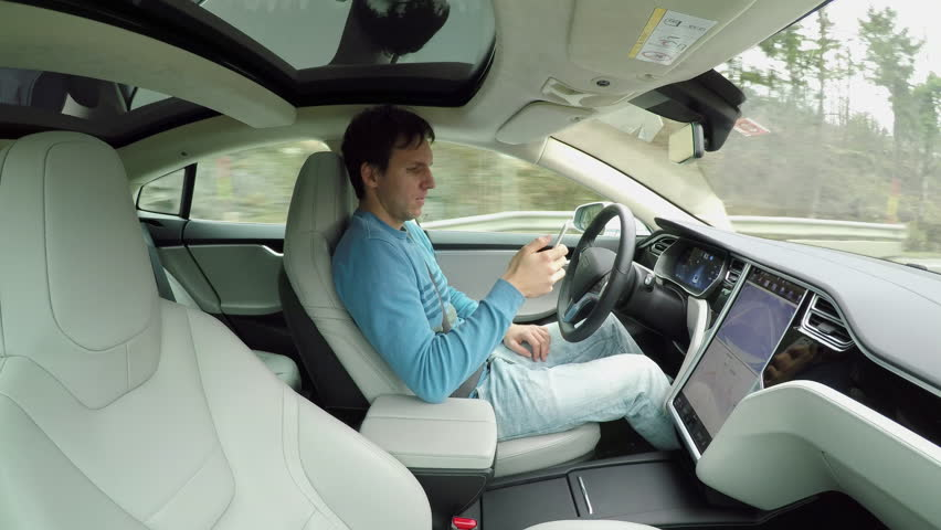Male driver writing messages on smartphone sitting behind self-driving steering wheel in autonomous autopilot driverless electric car traveling along the countryside road. Man texting in the vehicle #24508484