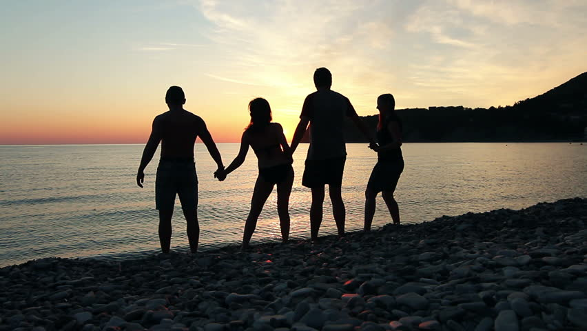 Group of people dancing on the beach at sunset, group of happy young people dancing at the beach on beautiful summer sunset