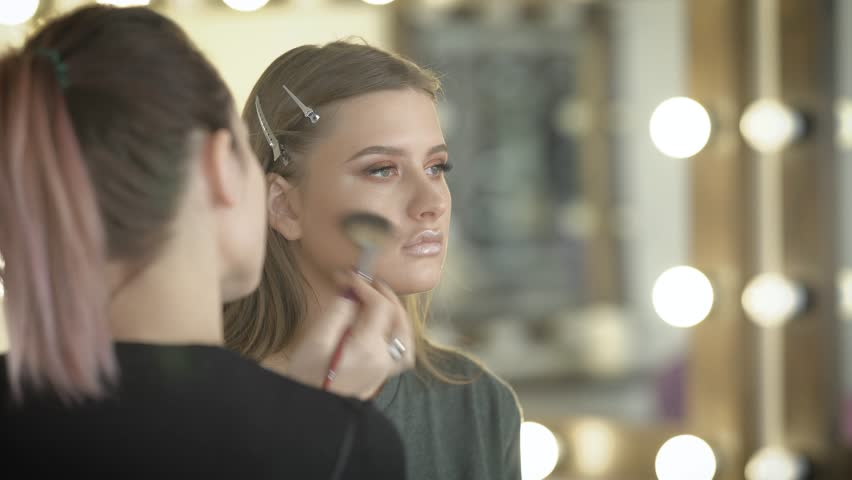 The girl in beauty shop. The master in a make-up trains the magnificent girl for a ball. The makeup artist puts a brush on a face of the client means under the name a highlighter. | Shutterstock HD Video #24532274