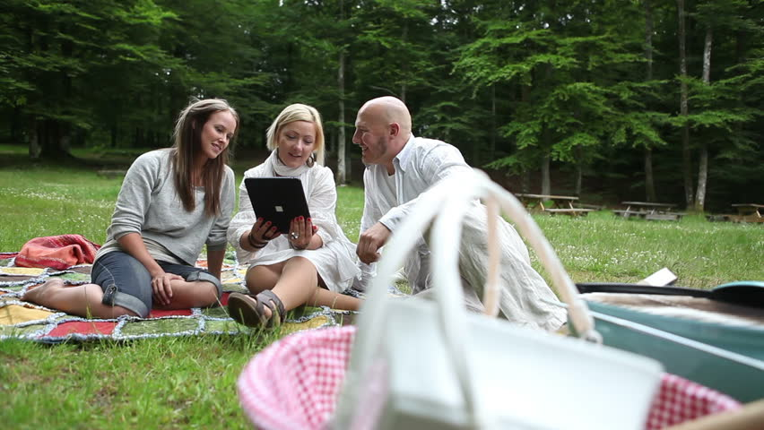 Three friends having fun at a barbecue in the park and looking at pictures on a tablet