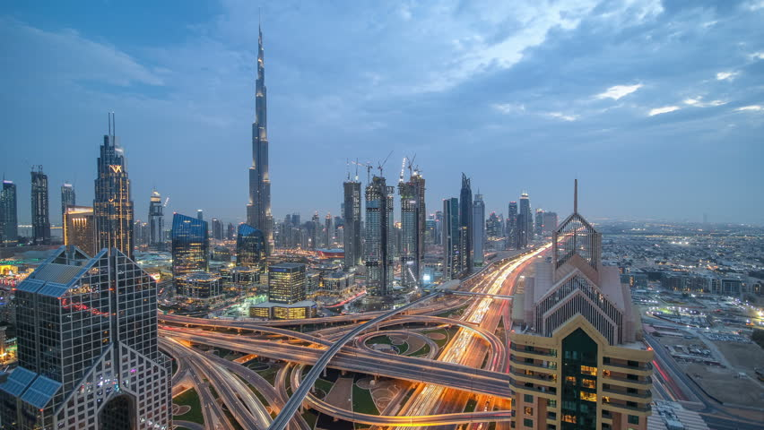 View on modern skyscrapers and busy evening highways day to night transition timelapse in luxury downtown of Dubai city. Top aerial view from tower rooftop. Road junction traffic. Dubai, United Arab