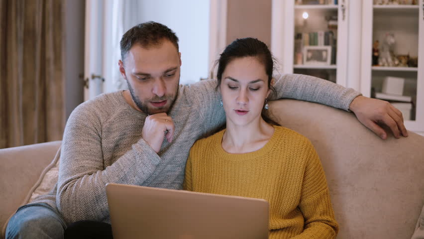 Young couple sitting on the couch and holding computer. Man and woman using laptop while sitting at living room. | Shutterstock HD Video #24559727