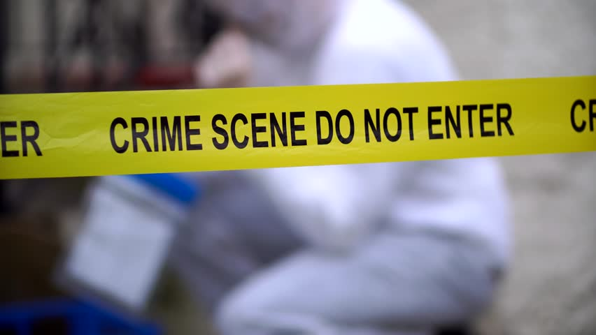 Crime Scene Do Not Enter. Police tape sign, murder investigation with forensic scientist in the background collecting evidence/ taking photographs. Domestic violence outside a house in the daytime
