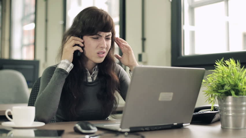 Angry businesswoman with cellphone and laptop and documents in the office