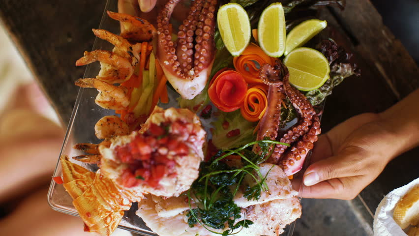 elaborate seafood platter being served at outdoor restaurant