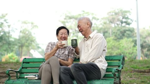 Slow motion Asian retired couple talking and drinking coffee in morning outdoor park