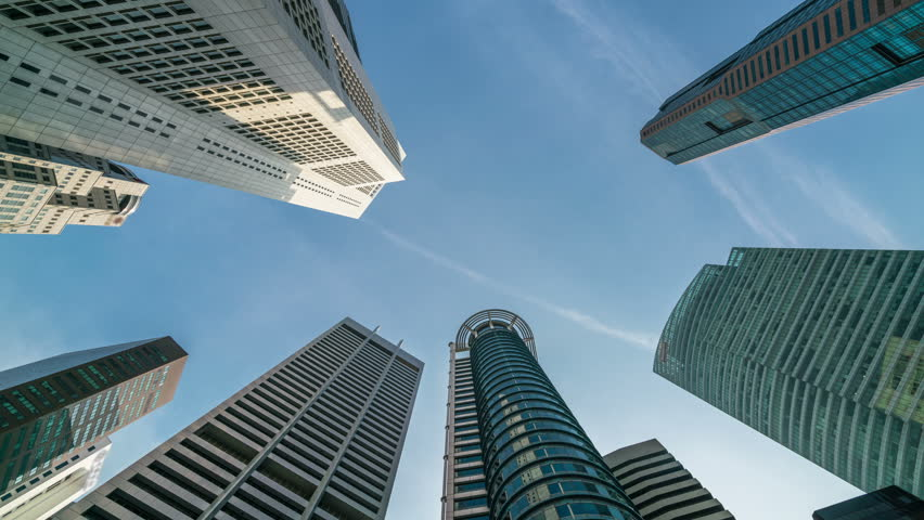 Time lapse - Looking up to business and financial skyscraper buildings in Singapore with slowly moving clouds in the sky at Singapore central financial district