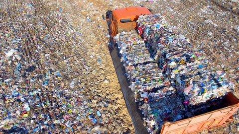 Truck unloading garbage, waste at landfill, junkyard. Aerial view.