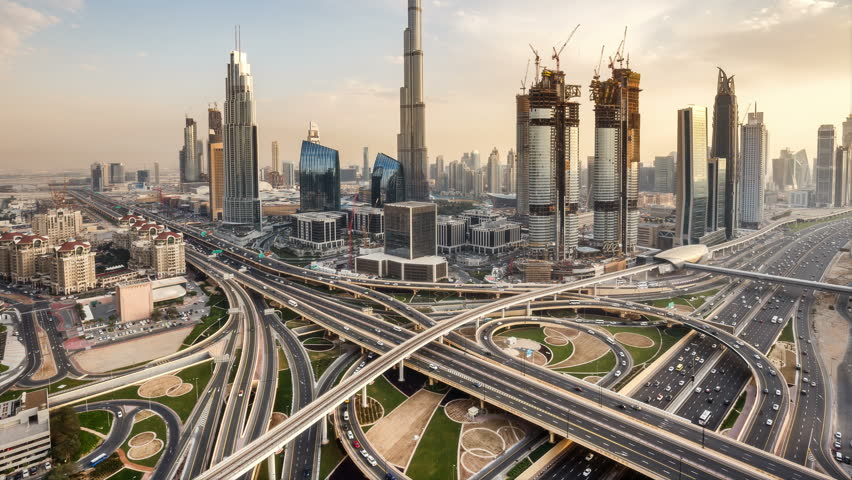 Spectacular daytime skyline of downtown Dubai, UAE. Scenic aerial view of famous highway intersection at sunset. Transportation and travel background. 4K time lapse.