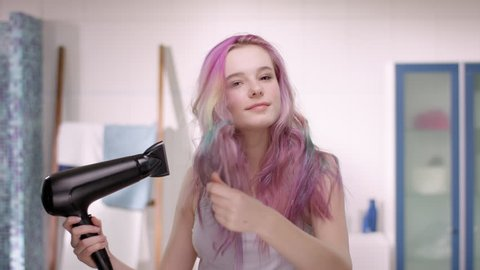 Young girl in puberty using a blow dryer before she is starting her day