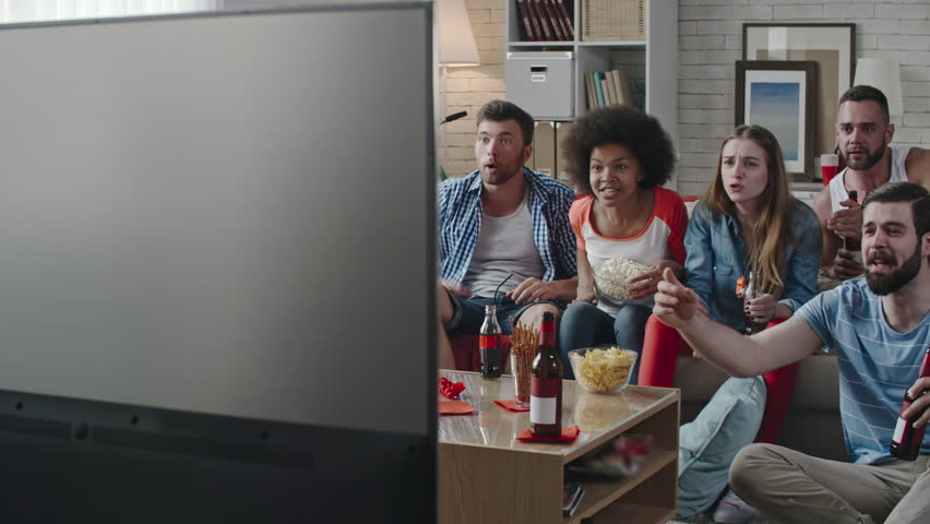 Tracking shot of company of friends sitting at home and watching sport competition on TV. They raising hands up and yelling when their team winning and girls hugging each other | Shutterstock HD Video #24648524