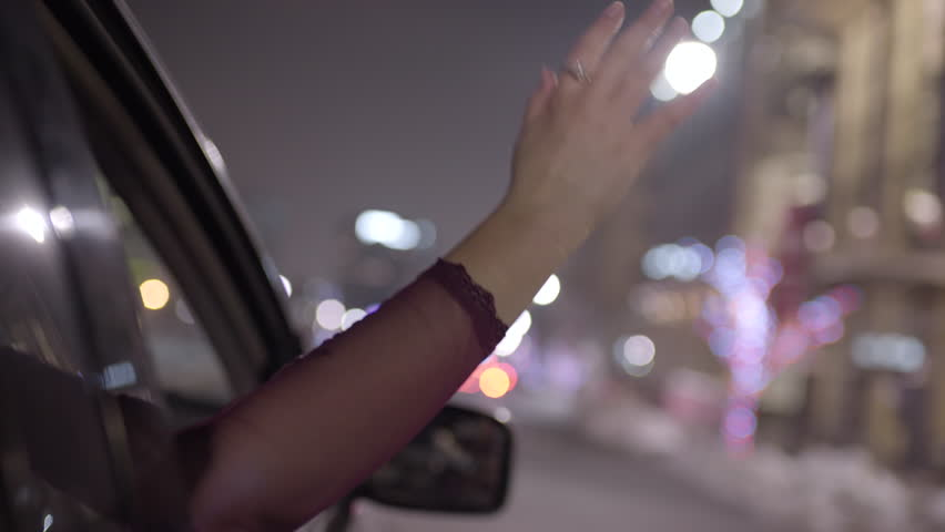 Young Woman Puts Her Hand Out Moving Car Window, Feels The Breeze At Night In City
