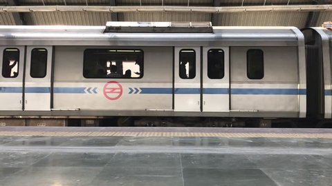 New Delhi, India - March 07, 2017: Delhi metro train stopped and run at a less crowded metro station in New Delhi in the noon time.