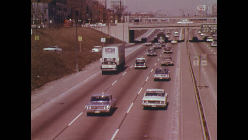 UNITED STATES 1970s: Traffic on highway / Car lowered from crane / Car in showroom / Pan across men at desks.