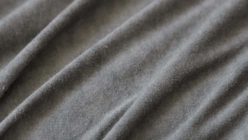 Tilting on dark grey smoked color fine t-shirt fabric close-up 2160p 30fps UltraHD footage - Silky gray modern clothing sample slow tilt 4K 3840X2160 UHD video