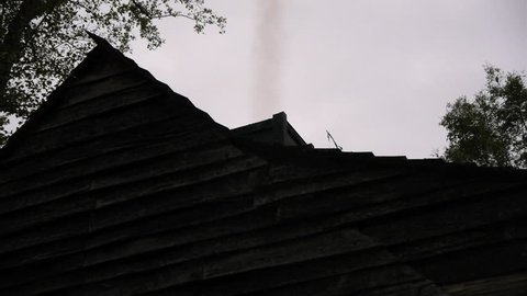 VIRGINIA - SPRING 2015 - Reenactment, Recreation. 17th - 19th century farm house with shingled roof, clapboard and wooden chimney - smoke from chimney. Colonial Jamestown, Plymouth plantation. America