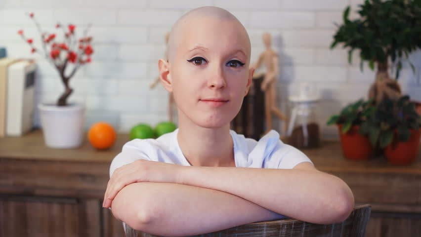 Portrati of a happy cancer survivor woman sitting on a chair, smiling and looking into the camera