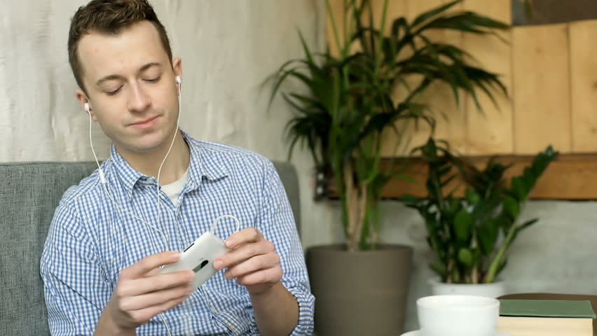 Young man listening music on earphones in the cafe and smiling to the camera  | Shutterstock HD Video #24704744